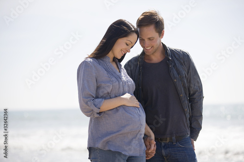 A pregnant woman and her partner standing on the beach