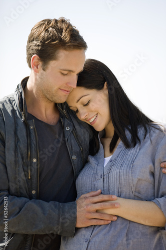 Portrait of a pregnant woman and her partner embracing