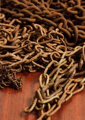 Rusty chain on wooden board