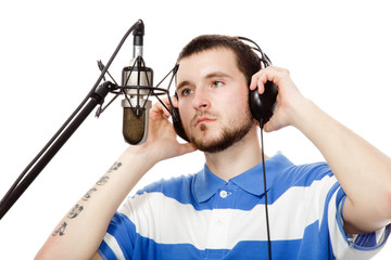 young guy with a beard, writes a song with headphones and a micr