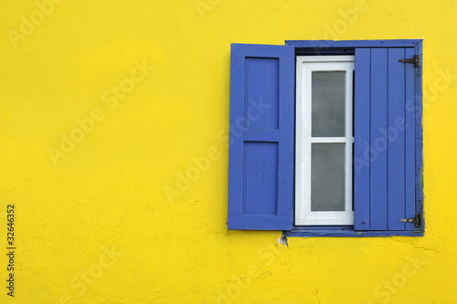 Fotobehang Caraïben Colorful yellow house with blue shutters in Governor's Harbour