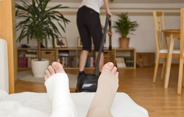 nach knie op alltag zuhause - frau saugt wohnung