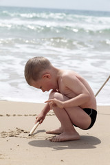 Little Boy draws fish in the sand beach