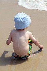 Little Boy in hat having fun on coastline