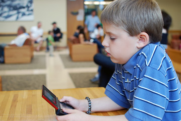 Boy Playing With a Small Computer Game