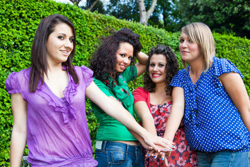 Teenage Female Friends with Hand in Stack