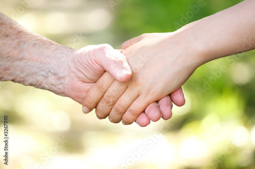 Photo: Senior and young women holding hands over shiny green ...
