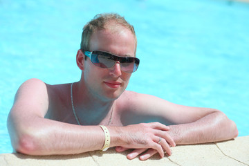 Portrait of a young handsome man in the pool
