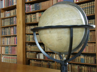 Rows of books on library shelves and a big globe