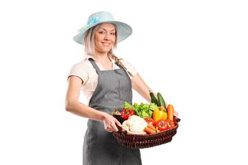 Smiling female farmer holding a basket of vegetables