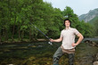 Young fisherman posing while fishing on a river with trees in th