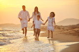 Fototapety happy young family have fun on beach at sunset