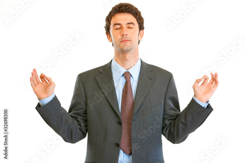 Meditating businessman with closed eyes isolated on white.