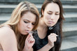 Two sad young girls smoke
