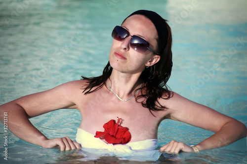 Young woman in the pool with a flower