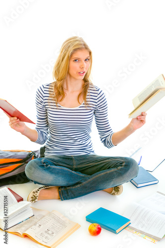 Shocked girl sitting on floor with books and preparing for exams