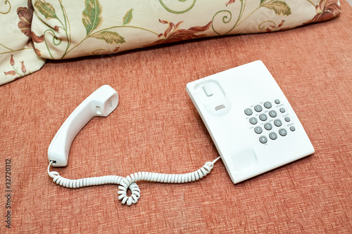 White telephone on sofa. Handset and phonebox