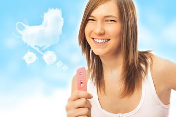 Portrait of young happy woman holding pregnancy test