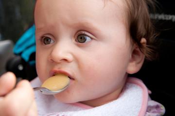enfant de 11 mois qui mange une compote