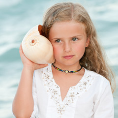 Beautiful girl with shell at the beach
