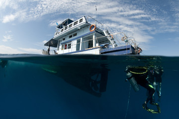 boat and scuba divers over under shot,half underwater