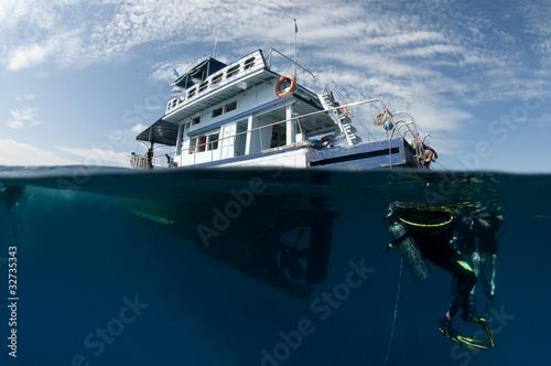 boat and scuba divers over under shot,half underwater - 32735343