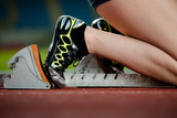 Detailed view of a female sprinter in the starting blocks poster