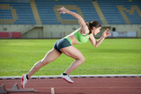 Action packed image of a female sprinter leaving starting blocks poster