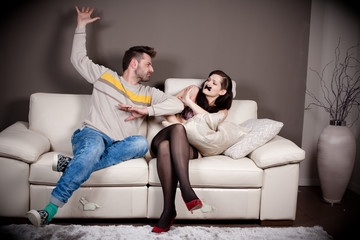 A man threatening to slap his girlfriend with taped mouth