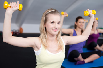 A small group of fit young woman lifting weights.Aerobics