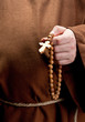 Hand holding wooden rosary