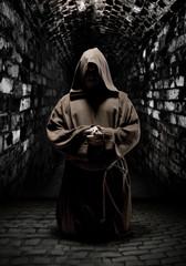 Praying monk in dark temple corridor