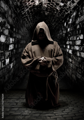 Praying monk in dark temple corridor
