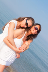 Two Female Friends Embraced on the Beach