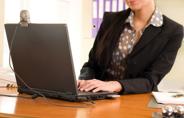 Business woman sitting in the office in front of the laptop