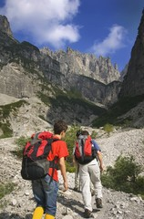 hikers climbing with backpacks up the dolomites; veneto, italy