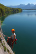 Young woman with climbing gear above alpine lake