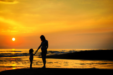 Pregnant mother and her child as silhouettes by the sea