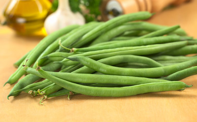 Fresh raw green beans on wooden board