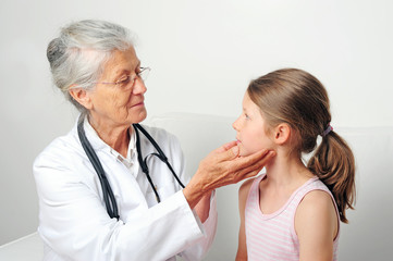 Ältere Kinderärztin untersucht Kind