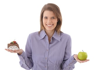 Happy woman offering cake and apple
