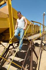 Мужчина спускается по металлической лестнице сложного механизма.