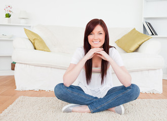 Attractive red-haired female posing while sitting on a carpet