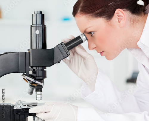 Attractive red-haired scientist looking through a microscope