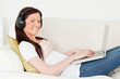 Good looking red-haired woman listening to music with headphones