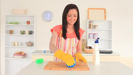 Young brunette cleaning the kitchen