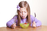 Fototapety A cute little girl looks in disgust at her bowl of vegetables