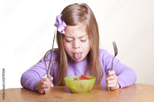 A cute little girl looks in disgust at her bowl of vegetables
