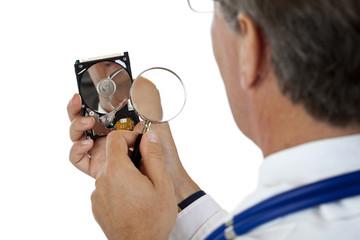 Doktor prüft Computer Festplatte mit Lupe auf Datenschaden