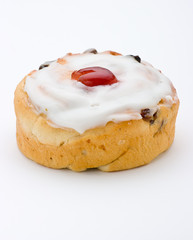 A round cherry cake with fruit current and white frosting on top